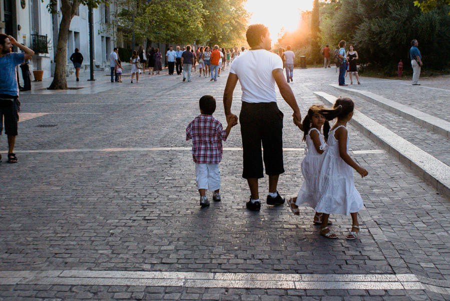 Man walking with three children on street of Athens, 2009. Photo by Ilias Antoniou.