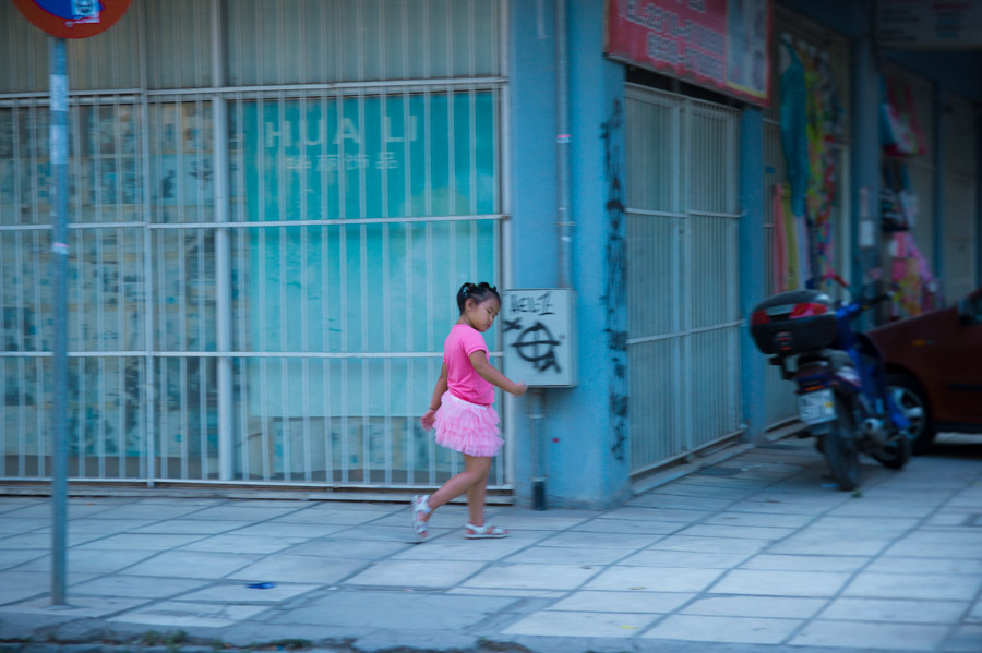 Asian child in pink walking on street at Thessaloniki. Photo by Ilias Antoniou.