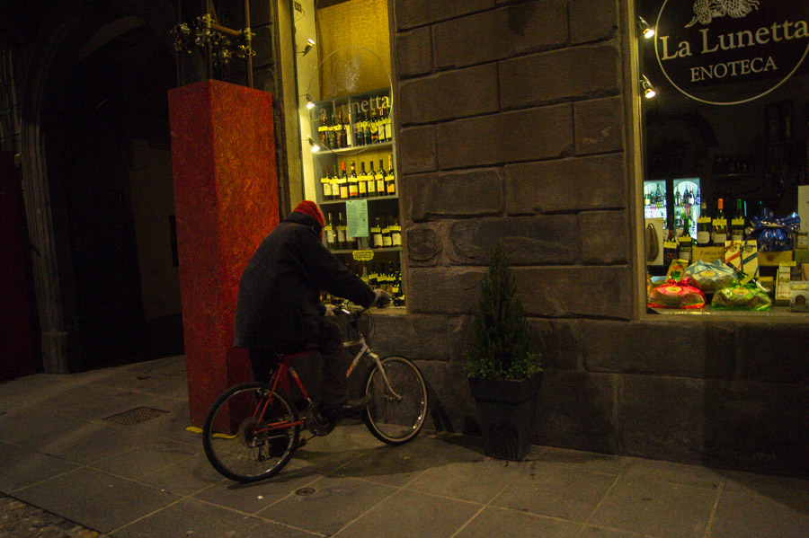 Man on bike outside store in Bergamo, Italy, 2013. Photo by Ilias Antoniou.