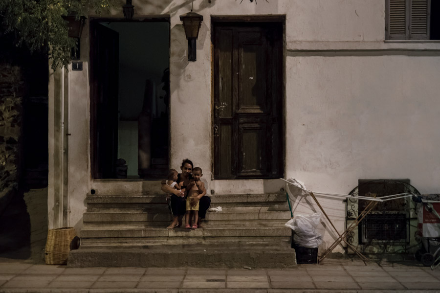 Woman with children sitting on stairs outside home, Thessaloniki, Greece, 2013. Photo by Ilias Antoniou.