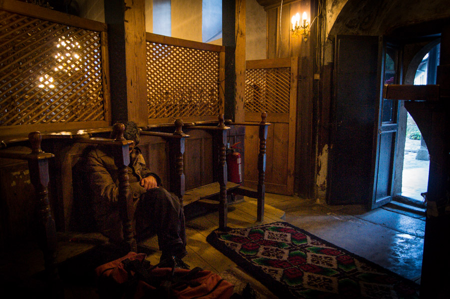 Homeless man siiting inside old Church in Bansko, Bulgaria, 2012. Photo by Ilias Antoniou.