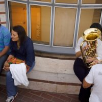 People and girl with trumpet sitting outside of an exhibition building. Street photography by Ilias Antoniou.
