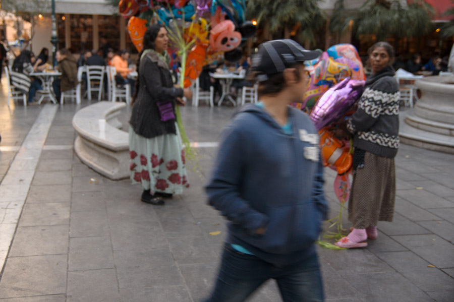Boy passing in front of women selling balloons. Photo by Ilias Antoniou, taken in Thessaloniki, November 2013.