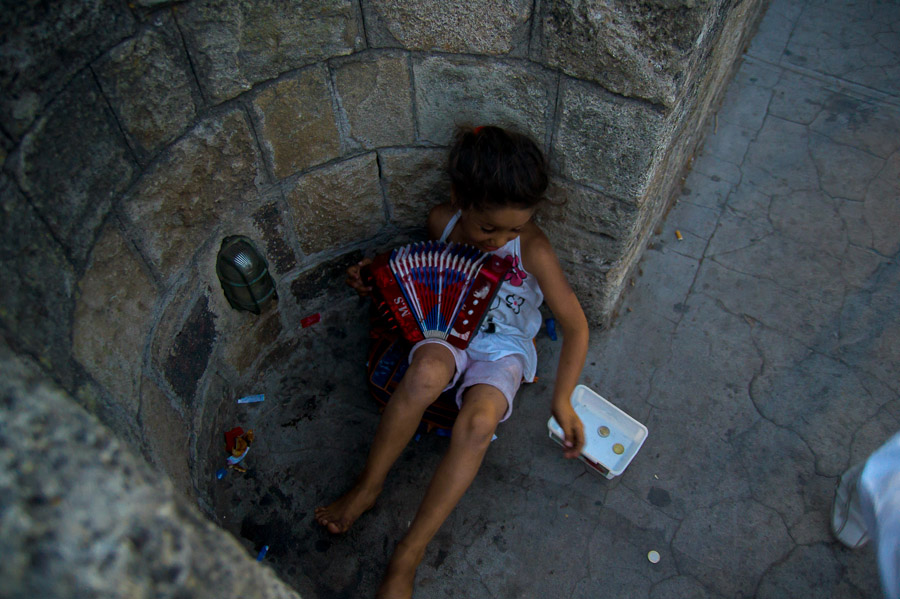Girl begging for money and holding accordeon, photo by Ilias Antoniou, taken in Rhodes, Greece