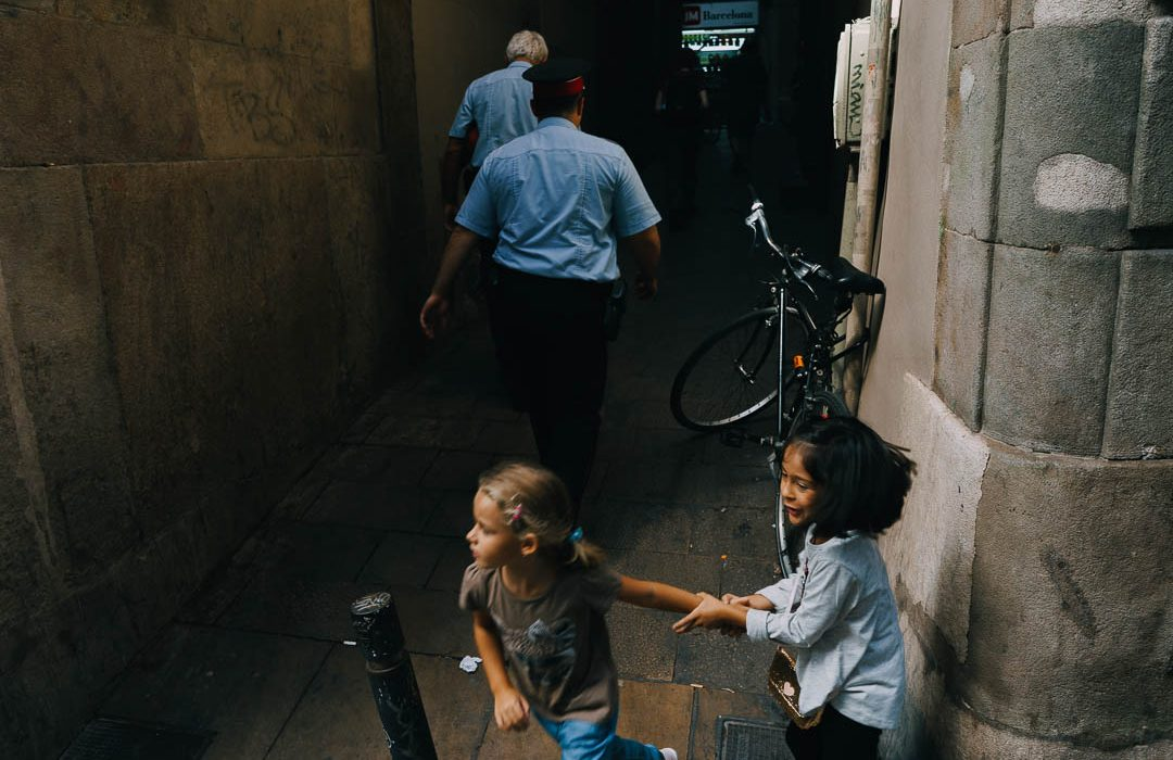 Street photography of cops and children running in Barcelona, Spain, 2016