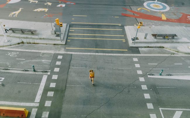 Barcelona, Spain / 2016 / Street photography of girl in yellow and red crossing a street, top view
