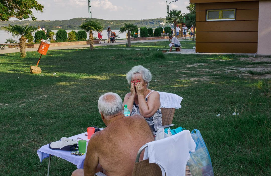 Old couple sitting near Doirani Lake during summer