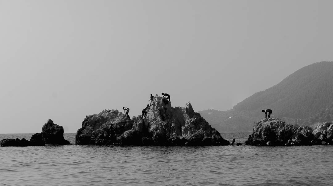 Pelion, Greece / 2015 / Black and white street photography of sea landscape with people climbing on rocks